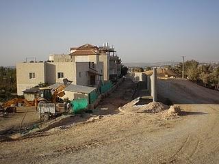 """""""החומה עוברת במרחק ממוצע של 40-50 מטר מבתי הכפר"""" - מתוך תצהיר המדינה. אחד הבתים שמבודד משאר הכפר עומד להיות מוקף בגדר תיל עם שער נעול ומצלמה שתעקוב אחרי הבאים ויוצאים ממנו. התמונה מתוך http://al-walaja.blogspot.com"""